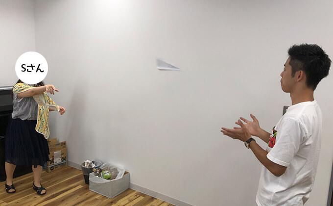 女性社員 紙飛行機投げる